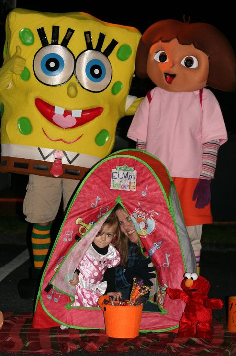 Spongebob and Dora behind a pink tent with a child and mother inside